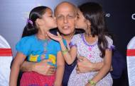 Spandan Chaturvedi as Chakor and Tasheen Shah as Imli place a peck on Mahesh Bhatt's cheek at the launch of Udann